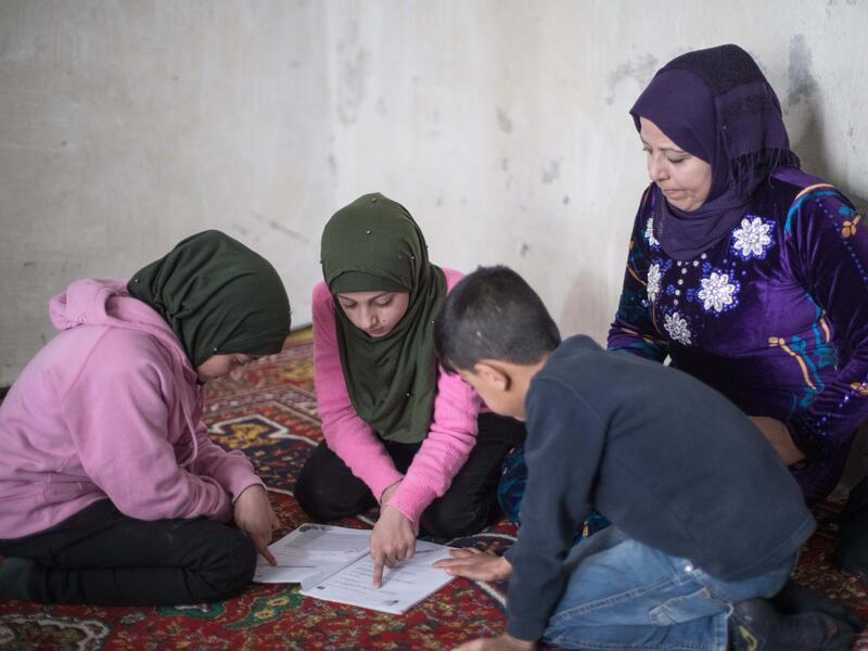 Reema sits on the ground with  her twins Shurouq and Shirina and their brother Eissa. Their children are looking at schoolwork while Reema looks over their shoulders.