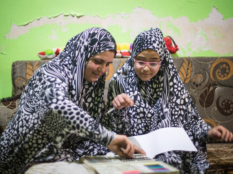 Wearing matching outfits, Ruba and Salam sit on a couch while Ruba helps her Salam with her homework.