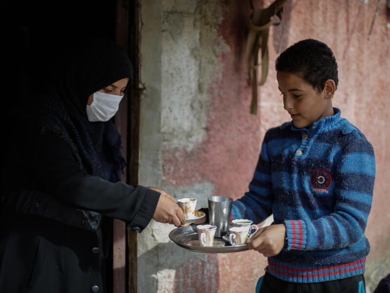 Tareq holds a tray with a tea pot and tea cups and offers it to his mom