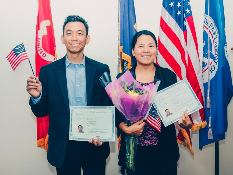 Two newly naturalized citizens smile with miniature American flags in hand with a U.S. flag and a Utah state flag in the background.
