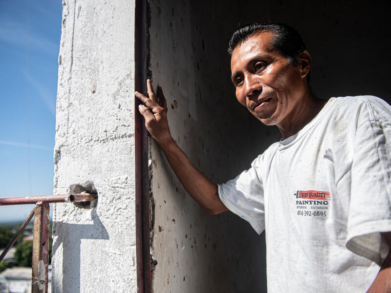 Reynaldo stands leaning against  the doorway of a church he is painting in  Zacatecoluca, El Salvador.