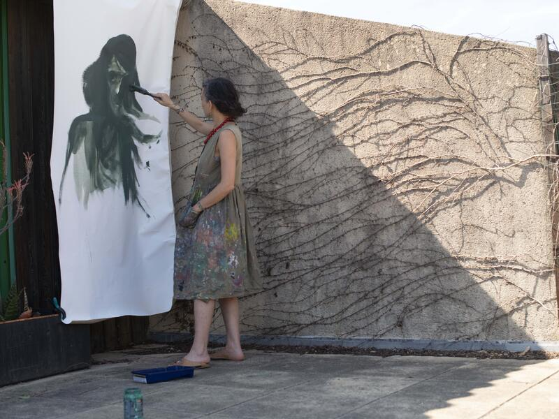 Diala Brisly, wearing a paint spattered smock dress, stads outside on a terrace painting a larger-rthan-life face on a sheet of paper hanging on the wall.