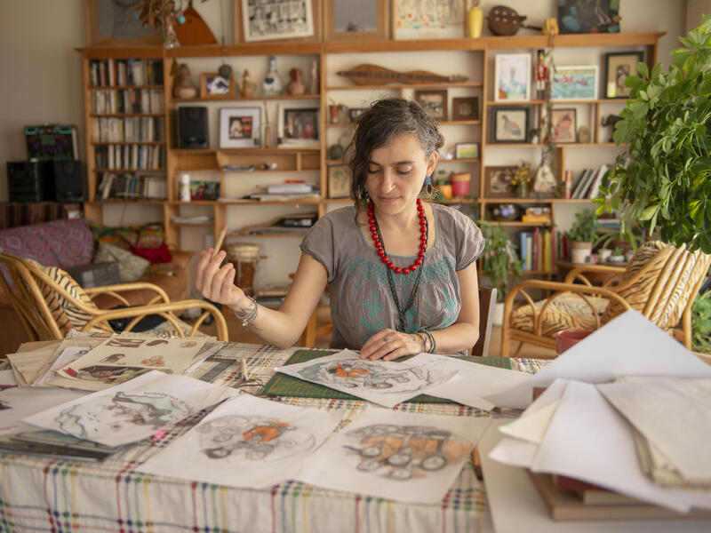"""Diala, sitting at her desk holding a pencil, reviews preliminary sketches of her """"Refugees are courageous"""" illustration."""