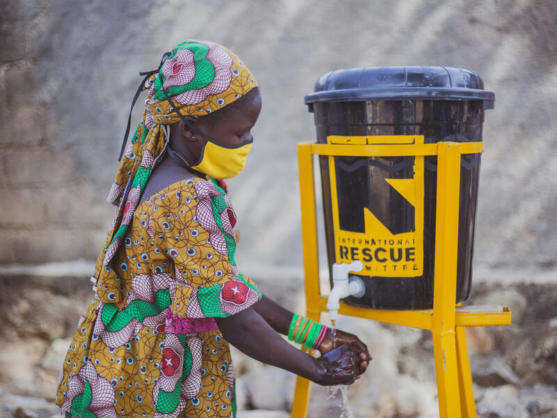 10-year old Anastasie, wearing a face mask to protect her against COVID-19 washes her hands at an IRC wash stand fashioned from a covered plastic bucket.