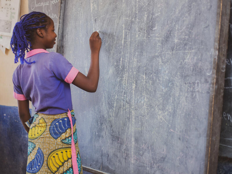 Kauvaumah, 11, smiles as she stands writing at a blackboard in her classroom in northern Cameroon.