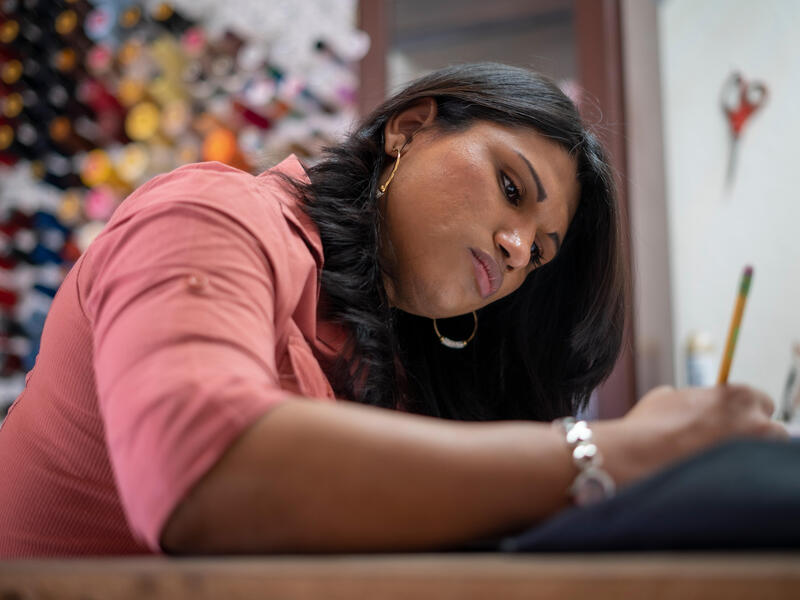 Lincy Sopall se sienta en un escritorio sosteniendo un lápiz y mirando una hoja de papel. Sus suministros para su estudio de diseño de moda están detrás de ella.