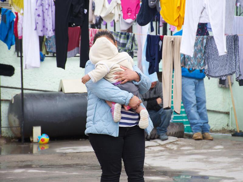 Alma, una solicitante de asilo de Guatemala, con su hija pequeña en un refugio apoyado por el IRC en México. Ella sostiene a su hija mientras se seca la ropa cerca de ellos.