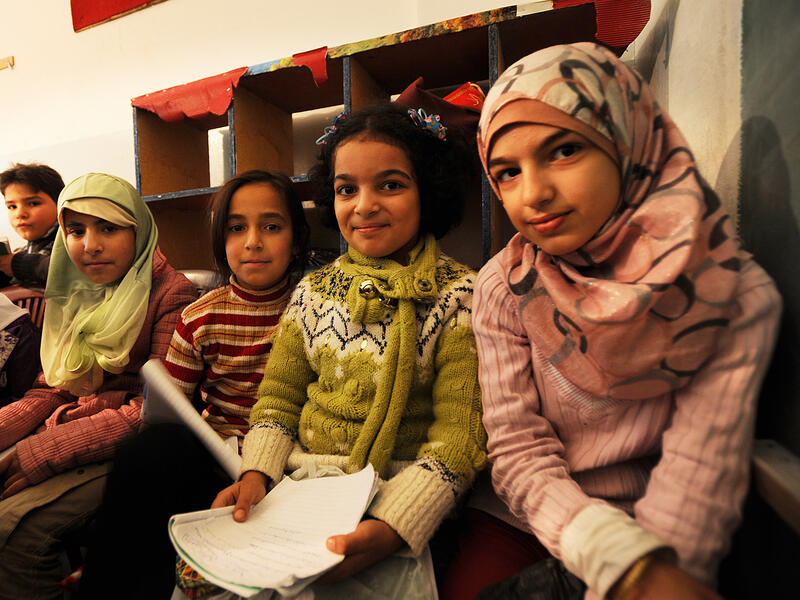 Four young girls sit next to one another in a school, looking at the camera and holding school supplies.