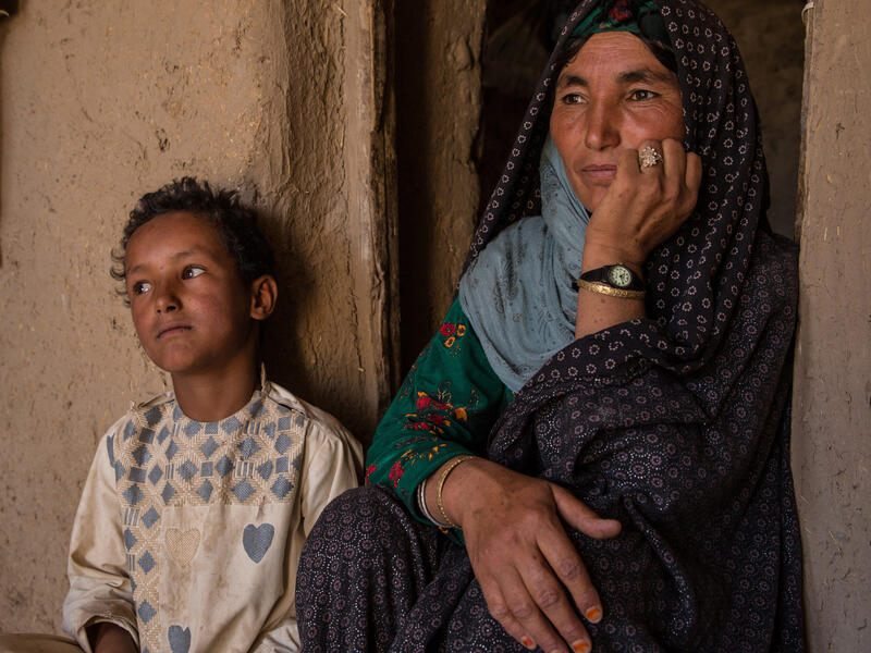 A mother sits against a wall next to her 7-year-old son.