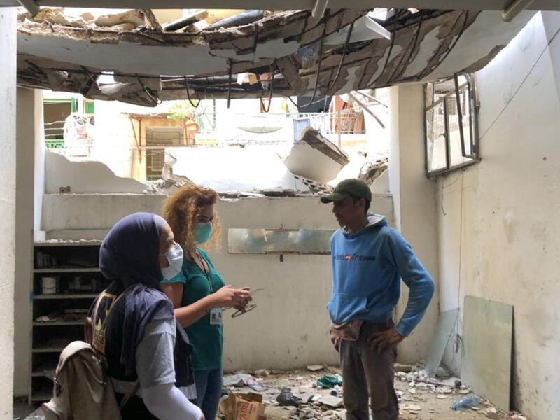 Three people stand, talking, in a damaged building. The ceiling is buckling, part of the front wall is missing and there is debris covering the ground.