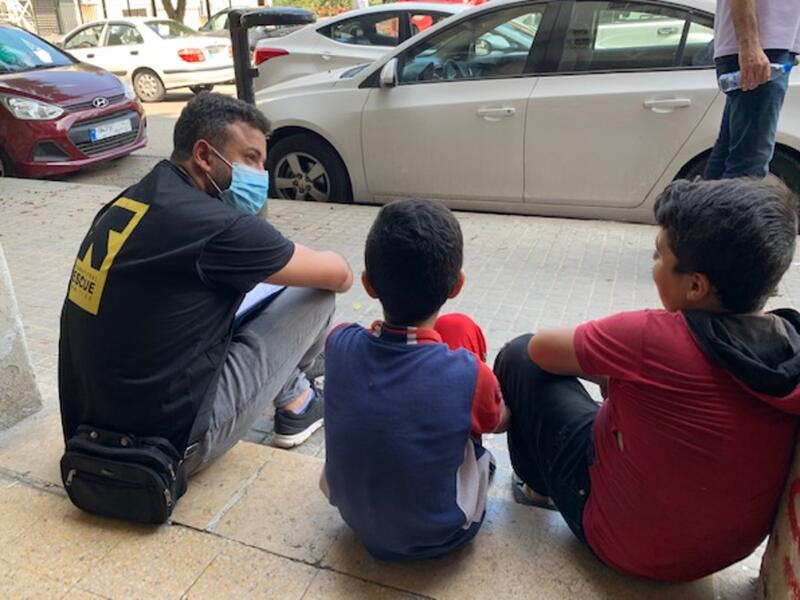 A man with an IRC vest sits on a curb with two young boys. They are all facing away from the camera and talking.
