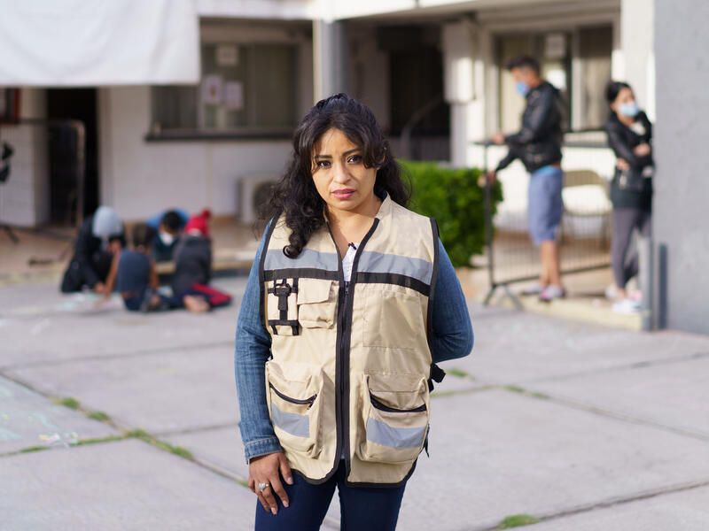 Rosa, wearing a brown vest with large pockets, stands in front of the triage hotel she helps manage in Ciudad Juárez, Mexico. In the background, children draw with chalk on the ground with their parents while other adults converse.