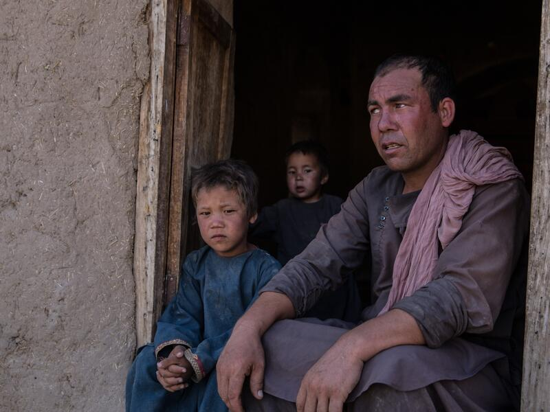 Abdul, 30, sits in a doorway with his children: Mujib, 1, Ismail, 3 and Ibrahim, 5.