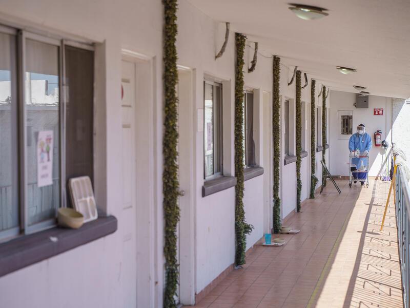Un trabajador de la salud con EPP completo empuja un carrito por las habitaciones de hotel.