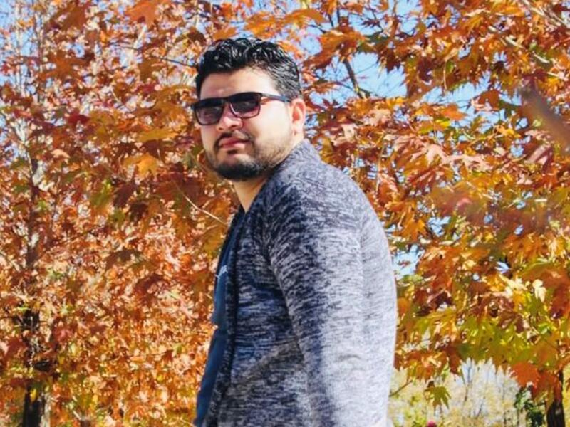 Ahmad looks at the camera while wearing sunglasses and standing in front of fall foliage.