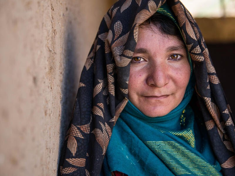 An Afghan woman looks at the camera while standing against a wall