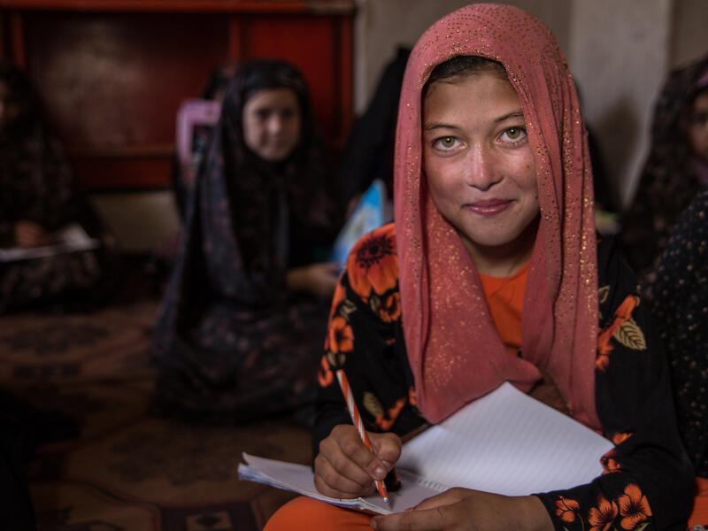 A young girl sits with a notebook on her lap ready to write while looking up at a teacher. There are other young girls sitting behind her.