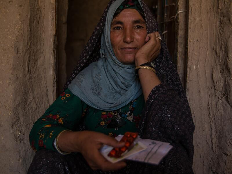 A  35-year-old Afghan widow sits in a doorway holding packets of medication she was able to get with the IRC's support.