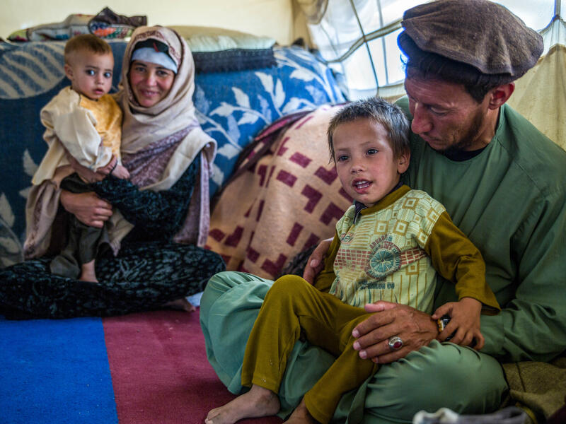 A family of four sit on rugs on the ground: a young boy sits on the lap of his father and a baby sits on the lap of her mother.