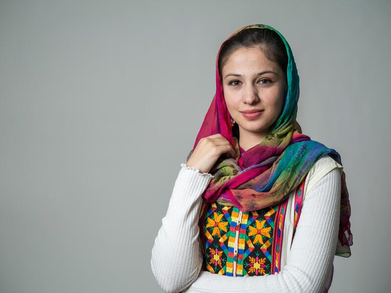 A portrait of Muska Haseeb on a grey background. She is a young woman in her early 20s wearing brightly colored clothes.