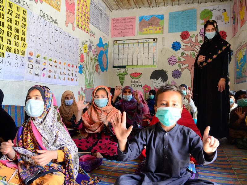 Children sit on the floor and a female teacher stands in a classroom, all are wearing masks and the kids are clapping.