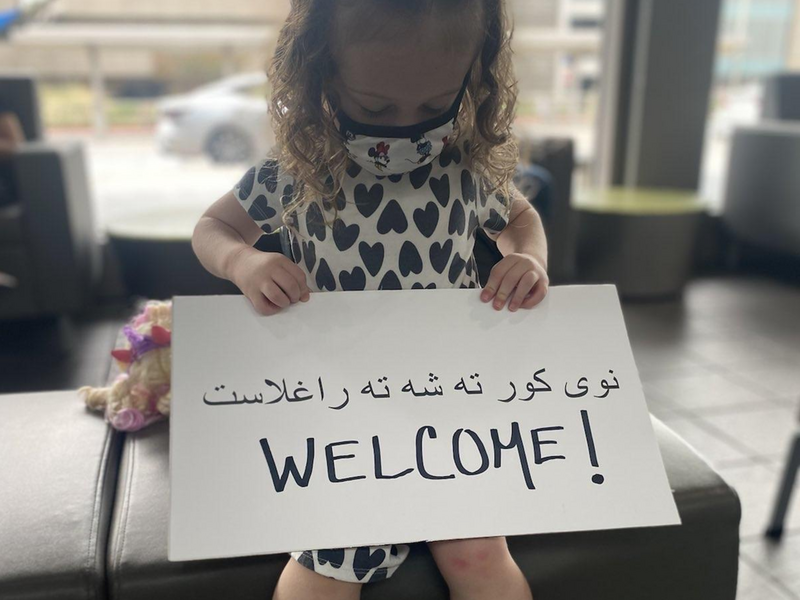 """A young girl holds a """"Welcome"""" sign in Pashto and English."""