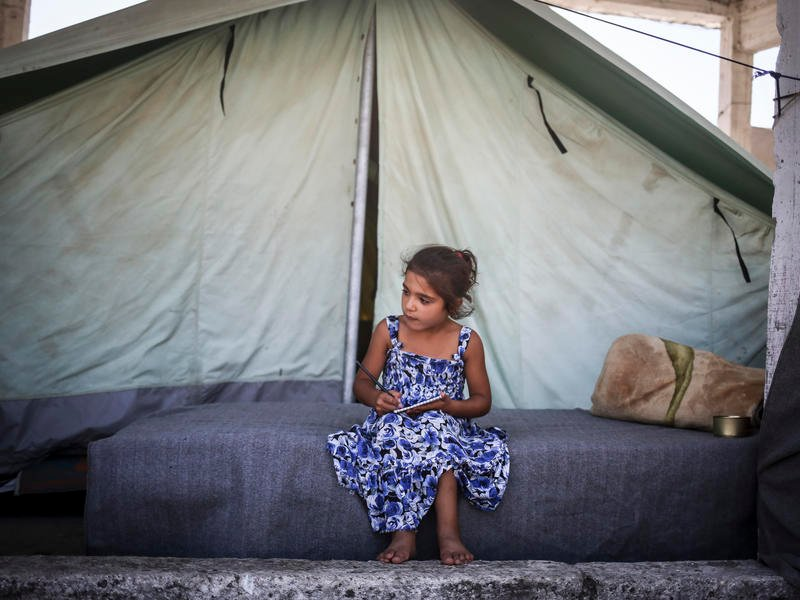 Seven-year-old sits outside her family's tent in the Alexandria refugee camp