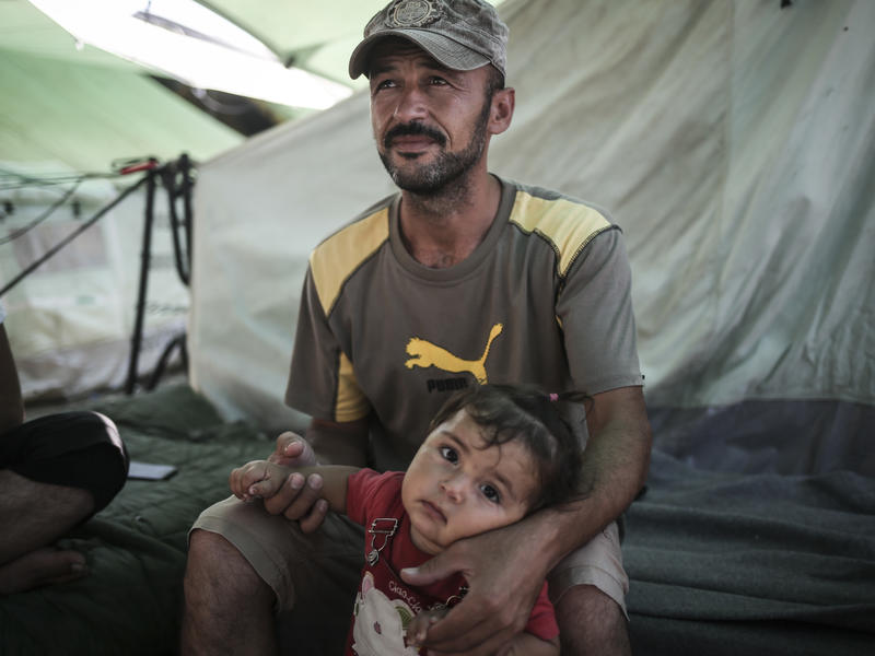 Father sits with his daughter outside their family tent in the Alexandria refugee camp