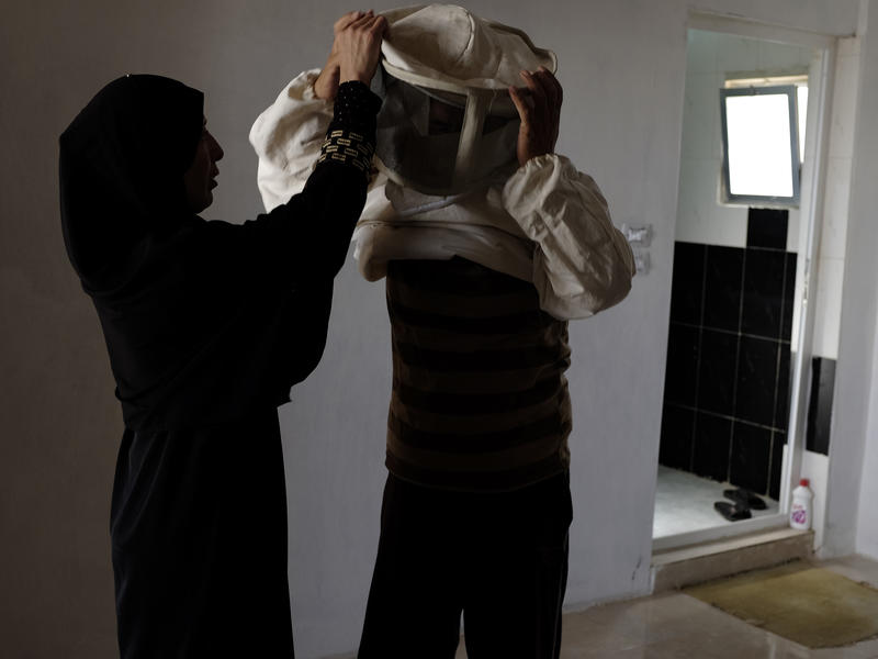 Syrian woman helps her husband put on his protective beekeeping suit