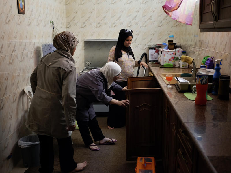 Two Syrian women plumbers visit a customer's home in Jordan