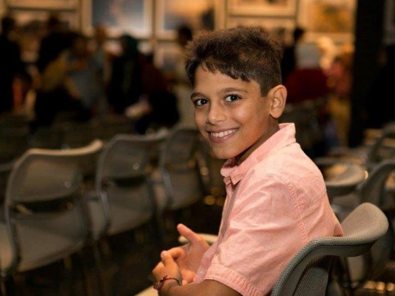 Syrian boy sitting in chair, smiling, at a UN Refugee Event in Los Angeles