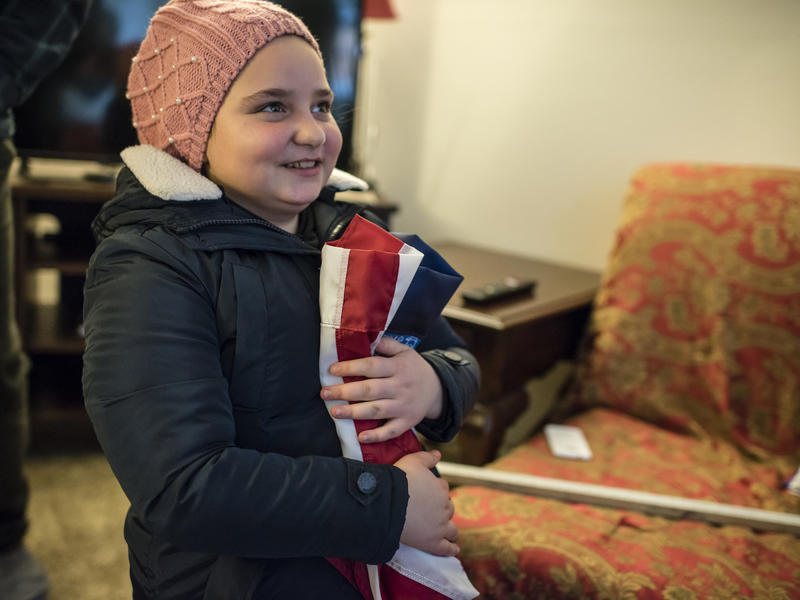 11-year-old Alaa holds a folded American flag