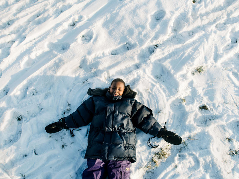 Muhammed creates a snow angel at a park in Boise
