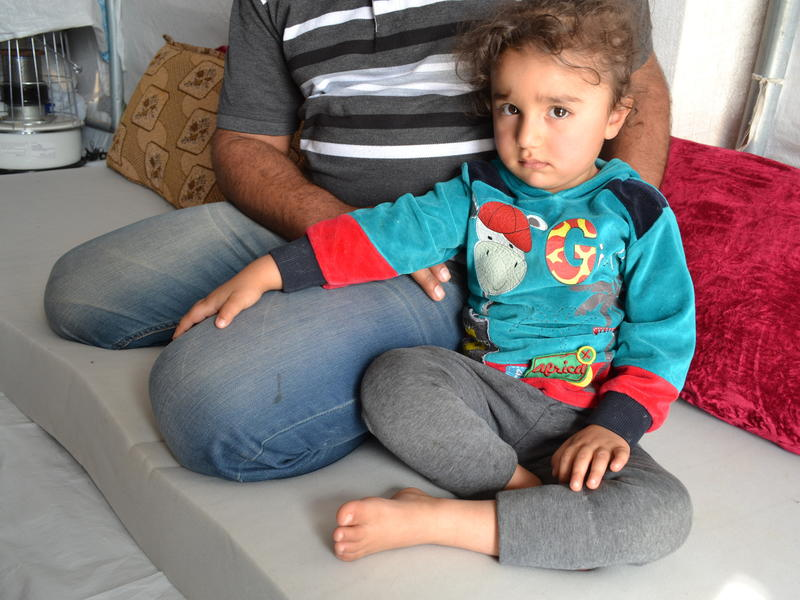 Khaled with his three-year-old daughter at the Khazer displacement camp