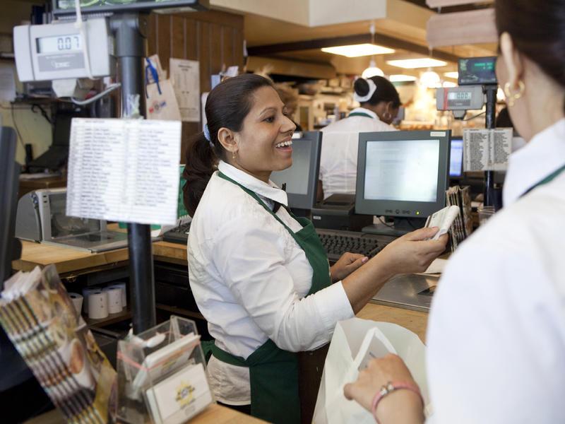 Uma rings up a customer at a gourmet market