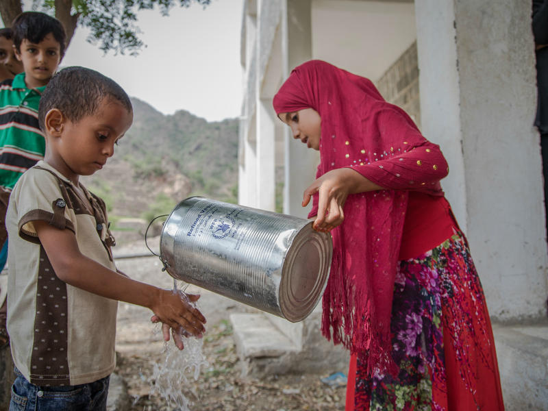A girl  holding a jug pours water over a boy's hands so that he can wash them.