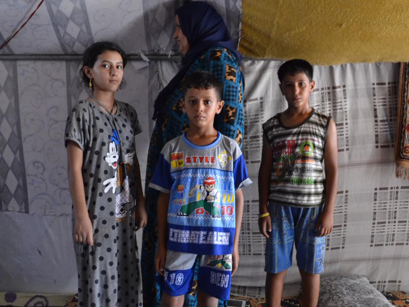 Abeer with her three children inside a tent in the camp near Baghdad