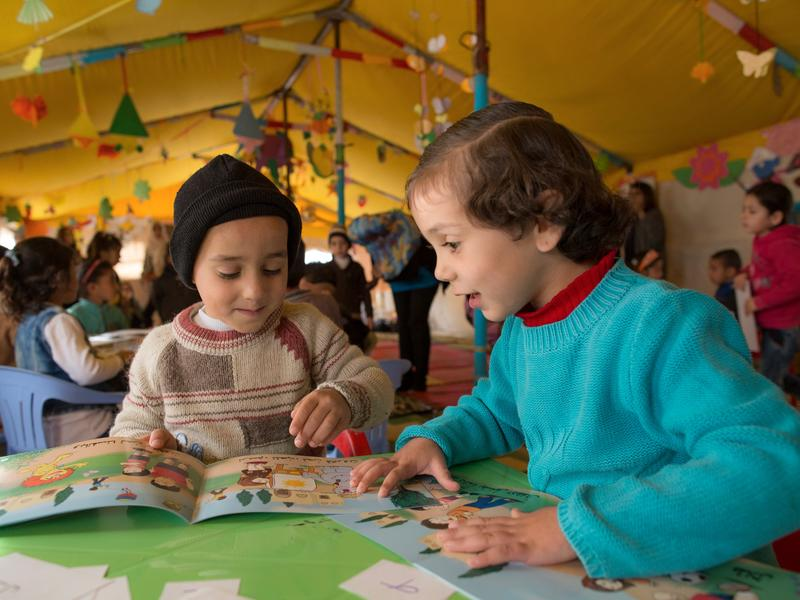 Two Syrian children read books in a tented classroom