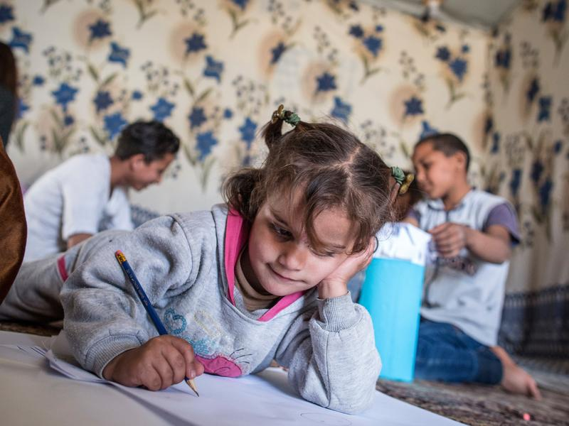 Young Syrian girl draws at home