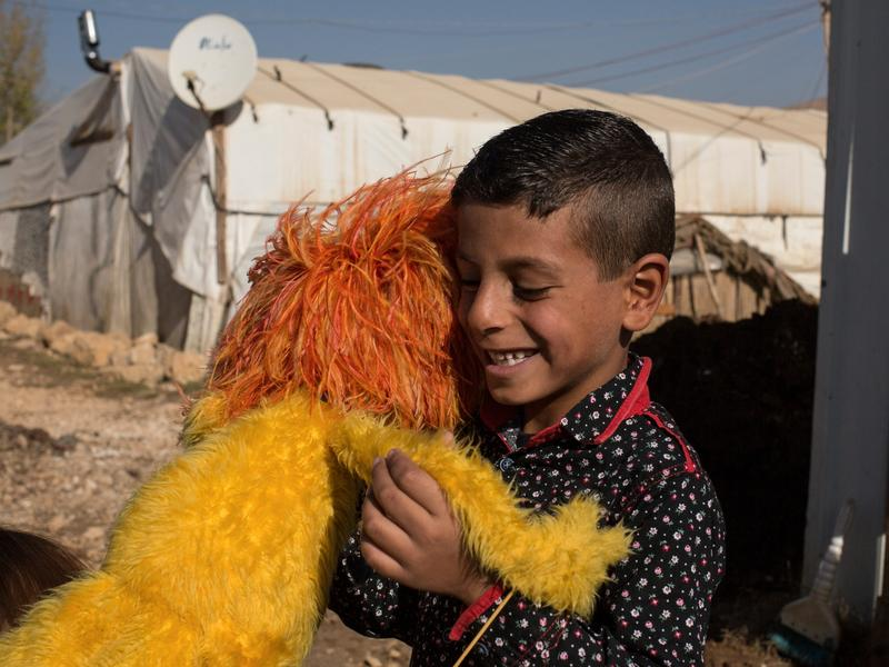 Syrian boy hugs Sesame Street Muppet