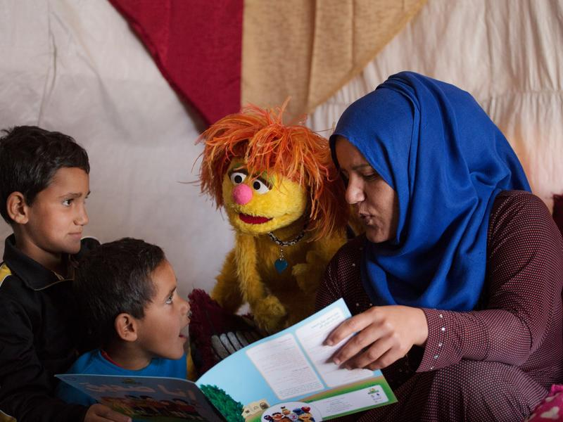 Syrian mother reads with her sons and a Sesame Street Muppet Tonton