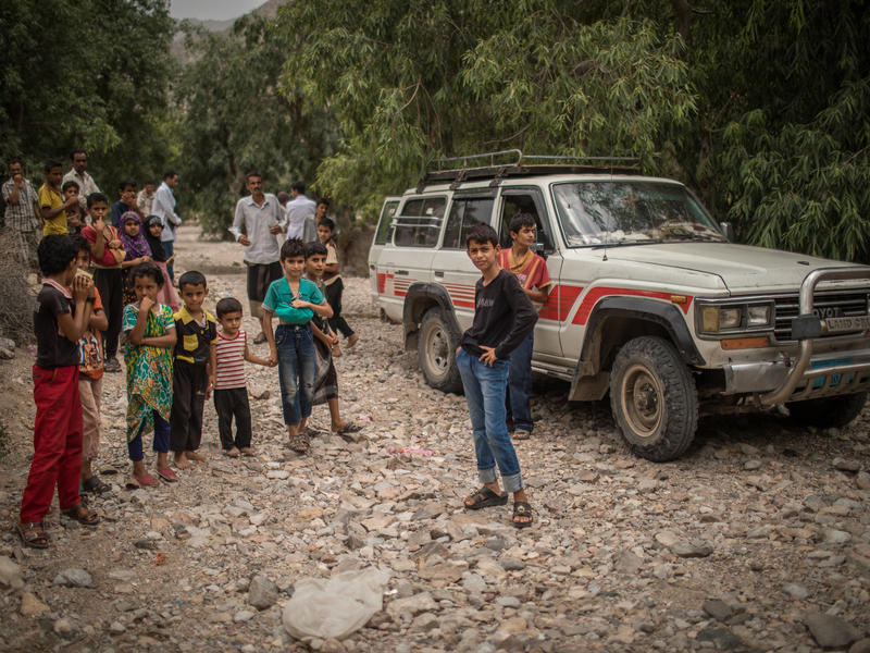 Children stand in front of an IRC mobile health team vehicle in a mountainous village in Yemen