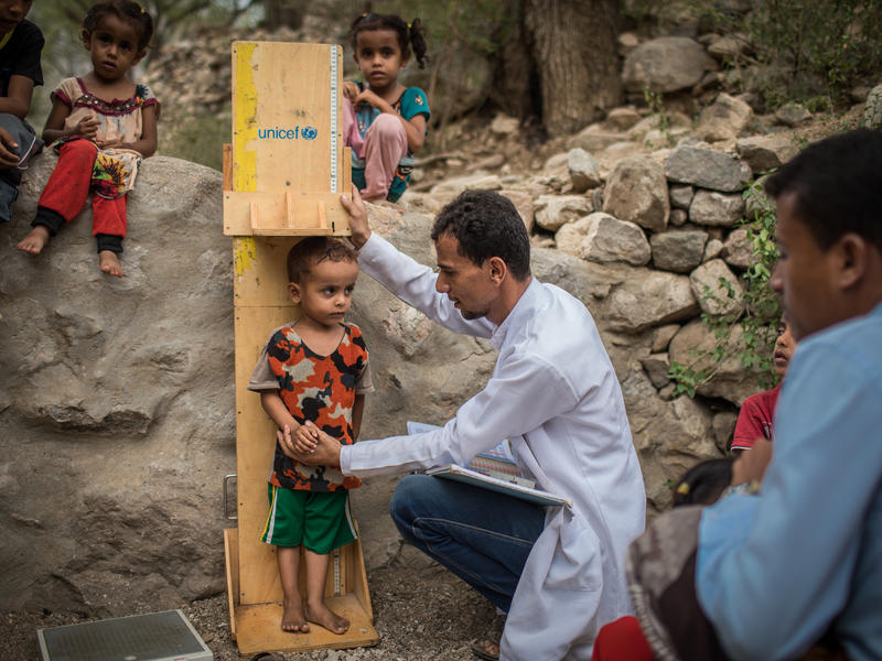 An IRC health worker measures a young boy as he screens him for malnutrition at an IRC mobile health clinic in Mosuk Village, Yemen