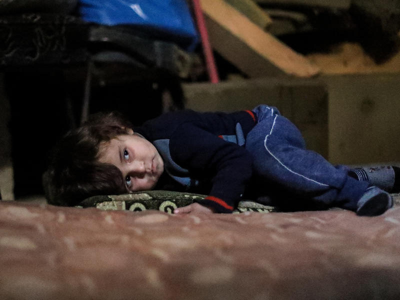 Syrian boy in underground bunker in Eastern Ghouta lying down