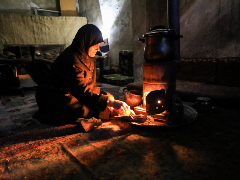 A Syrian woman cooks in her underground shelter in Eastern Ghouta.