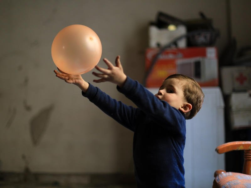 Syrian boy in underground bunker plays with a balloon