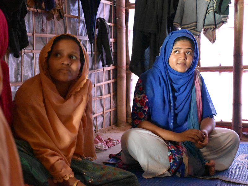 Two Rohingya women sit on mats, listening to an aid worker talk about monsoon preparedness in their refugee camp
