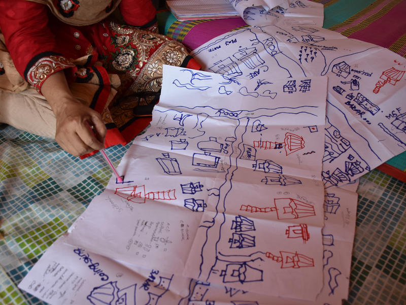 An aid worker uses a map of the refugee camp to indicate areas at risk of flooding or landslides during the monsoon rains.