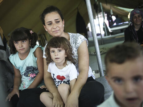 A Syrian refugee woman sits with her son and other family members inside a tent.