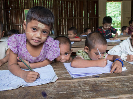 Refugee children hold pencils in a classroom at a refugee camp in northern Thailand